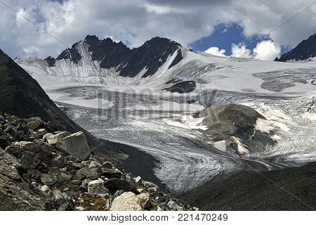 Huge ice field of the glacier at the foot of mount Iiktu, the main peaks of the South-Chuya ridge in the Altai mountains. Heavy snow clouds covered the sky over the glacier.