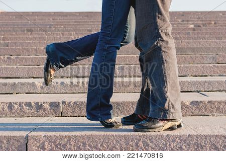 Young couple hugging on stone staircase steps. Woman flirty lifted her leg.