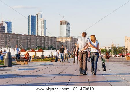 MOSCOW, RUSSIA - June 30, 2009. Young loving couple walking on Poklonnaya Gora, Victory park. Other people resting, rollerblading, doing summer leisure activities. Construction of Moscow-City business center on background.