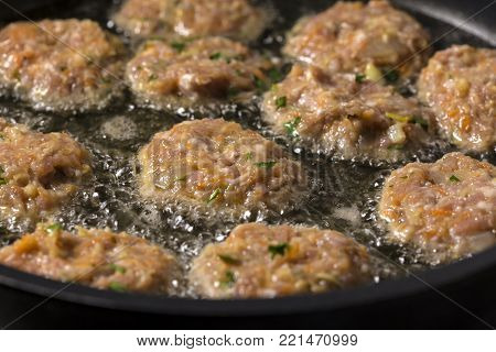Frying large homemade Romanian meatballs parjoale or chiftele in pan for dinner.