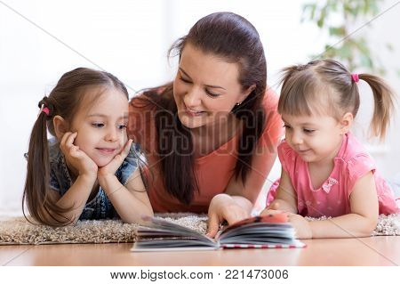 Family - mother and children daughters lie on floor and read book together
