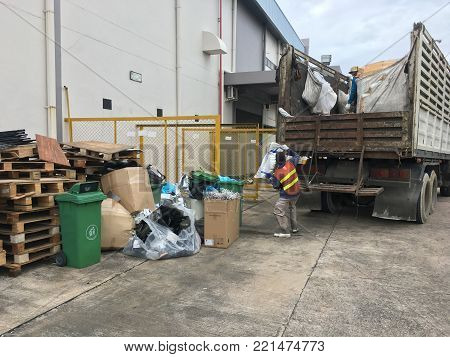 Workers are collecting garbage into garbage trucks.