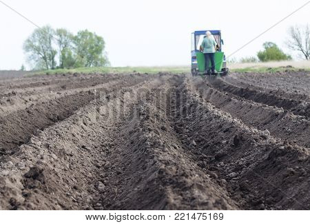 Concept: farming, Planting plants and various crops with the help of a planting machine. Spring works in the field, planting spring works in the garden