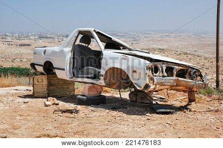 Abandoned white car remains on desert landscape