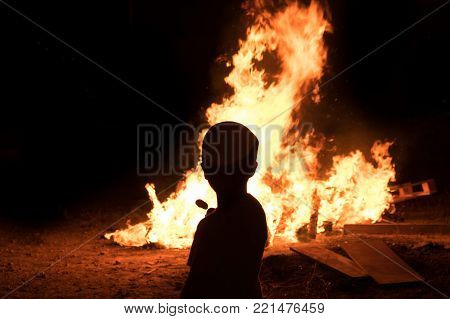 Little jewish boy do marshmallow candy near to bonfires at Jewish holiday of Lag Baomer