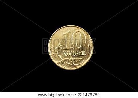 A super macro image of a gold Russian ten kopeck coin isolated on a black background