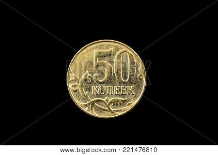A super macro image of a gold Russian fifty kopeck coin isolated on a black background