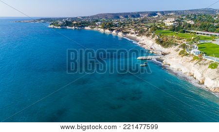 Aerial view of coastline and landmark big white chalk rock at Governor's beach, Limassol, Cyprus. The steep stone cliffs and deep blue sea waves crushing in coves and dark sand next to Kalymnos fish restaurant from above.