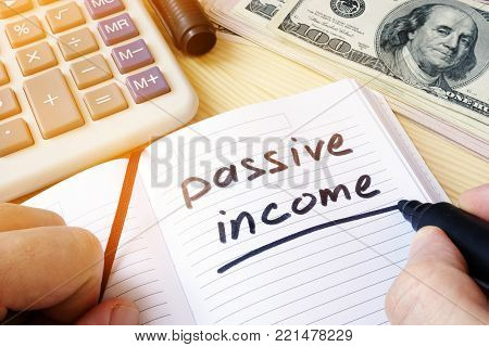 Passive income written in a note and money.