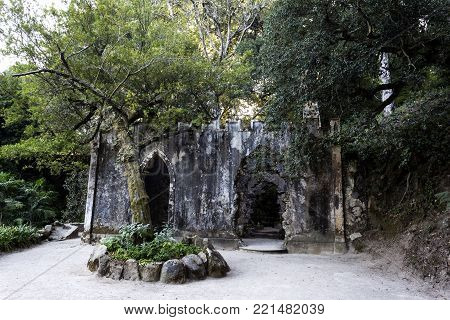 MONSERRATE, PORTUGAL - October 3, 2017: View of the fake ruins of a chapel, a popular romantic concept of the 1800s, being overrun by an Australian Banyan tree (ficus macrophylla) near Sintra