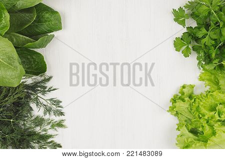 Different green sheaves greens for spring salad on white wooden background, top view, decorative frame.