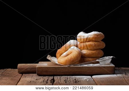 Sweet donuts with powdered sugar on a black background. Tasty, but harmful food on an old wooden table with copy space.