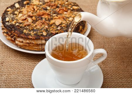 Tea is poured into a cup from porcelain teapot with homemade chocolate puff cake on the background. Selective focus on teapot