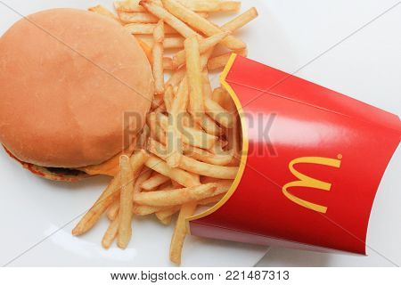 MOSCOW, RUSSIA - DECEMBER 9, 2017: McDonald's Burger and Fries Fast Food Meal on White Plate. McDonald's Corporation is an American Fast Food Restaurant Chain, Founded in 1940, Popular Worldwide.