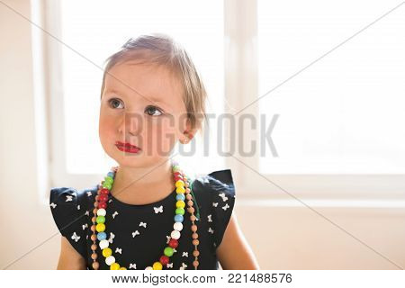 Cute little girl in pretty dress at home wearing big necklaces and red lipstick.