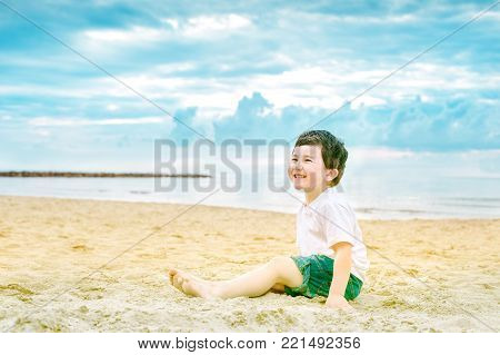 Cheeful child sitting on a sandy beach and laughing