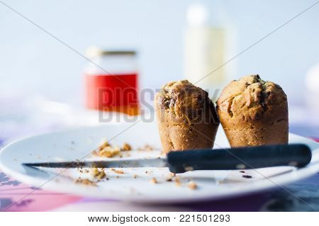 Homemade muffin over a plate with a knife a few crumbs around, in the background a jar of honey