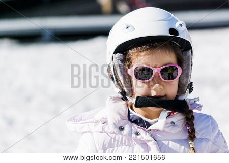 5 year old girl dressed to go skiing with helmet and glasses, dressed in white and pink looks inside the camera