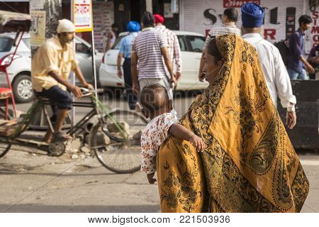 DELHI INDIA - July 15 2015 : beggar nursing mother in chandni chowk in old delhi, Normally homeless person live in marketplace of delhi.
