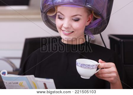 Young woman female client reading magazine and drinking hot beverage coffee tea in hairdressing beauty salon. Girl in hair rollers curlers with hairdryer dryer relaxing by hairdresser hairstylist.