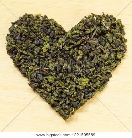 Diet healthcare concept. Green tea heart shaped on wooden surface. Healthy food drink for lower heart disease risk