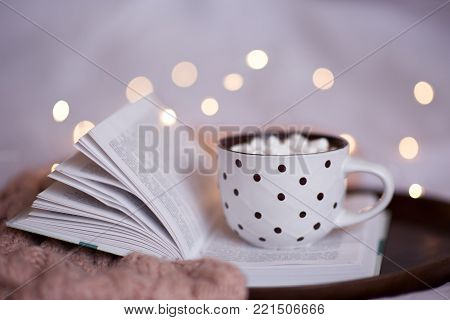 Cup of coffee staying on opn book in bed close up. Good morning. Breakfast.