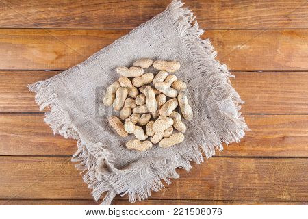 Not peeled peanuts on sackcloth on wooden background