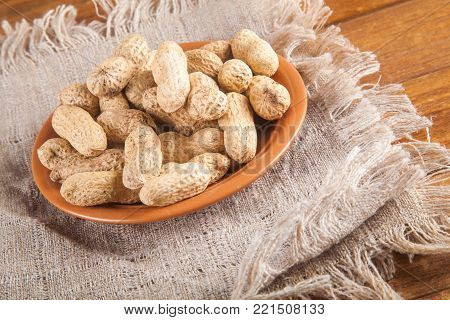 Not peeled peanuts in the plate on sackcloth on wooden background