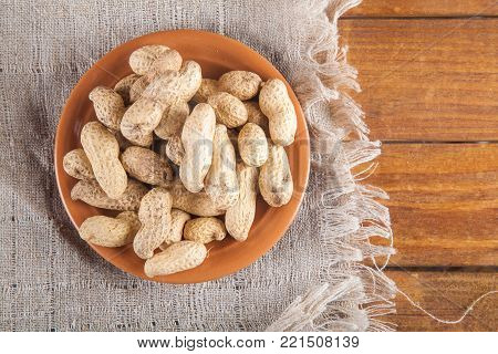 Not peeled peanuts in the plate on sackcloth on wooden background. Top view