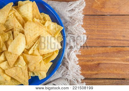Nachos corn chips in blue plate on sackcloth on wooden table with copy space. Top view