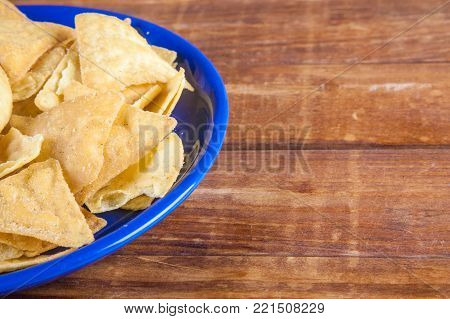 Nachos corn chips in blue plate on wooden table with copy space