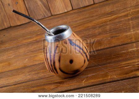 Calabash and bombilla on dark wooden background