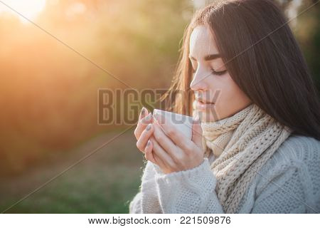 A young girl holding a cup of hot drink and smiling at the background of a autumn forest. Attractive young woman in autumn outdoor. Female model drinking hot tea in the autumn forest, close up