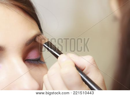 Female beauty. Makeup artist stylist applying with brush cosmetic on eyebrow of young woman. Girl by visagiste. poster