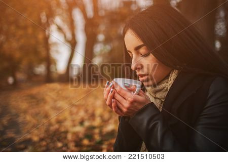 A young girl holding a cup of hot drink and smiling at the background of a autumn forest. Attractive young woman in autumn outdoor. Female model drinking hot tea in the autumn forest, close up.