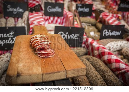 Tasty cut sausage placed on wooden board in delicacy shop