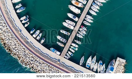 Aerial bird's eye view of Zygi fishing village port, Larnaca, Cyprus. Bird eye view of aligned fish boats moored in the harbour, docked yachts, pier, wave breaker rocks near Limassol from above.