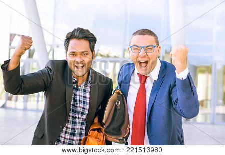 Interracial businessmen exulting looking at camera outdoor - Successful couple of multiracial men fist pump gesture standing outside - Multicultural concept of teamwork , success, business and triumph