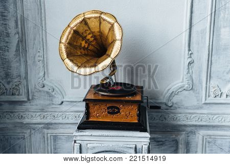 Old record player against ancient wooden wall. Antique gramophone with retro plate produces pleasant sounds or music. Stereo system. Revolution and sound technology concept