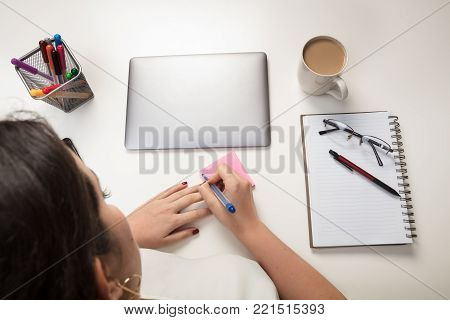 Woman writing a sticky note reminder for herself as she sits working at a desk with a closed laptop and notepad with pen and glasses in an overhead view Woman writing a sticky note reminder for herself as she sits working at a desk with a closed laptop