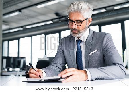 Mature businessman in gray suit sitting at desk in the office, writing something into his personal organizer.