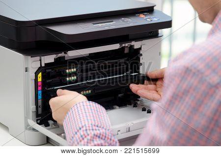 Man replacing toner in laser printer. toner printer cartridge print laser office supplies refill concept