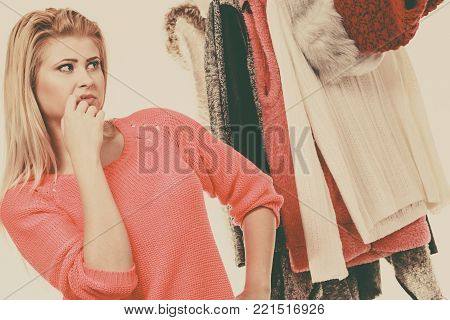 Young woman indecision in wardrobe, teen blonde girl choosing her warm winter fashion outfit in walk in organized closet. Shopping store clothing rack. Toned image