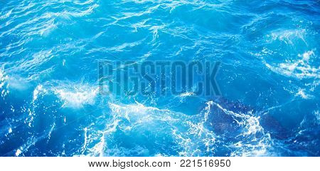 Background image of aqua sea water surface with sunny reflections splitted by waterline, aerial view. Ocean wave close up
