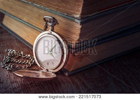 dial Vintage pocket watch on a chain and old books on a wooden background. Tinted picture in low key