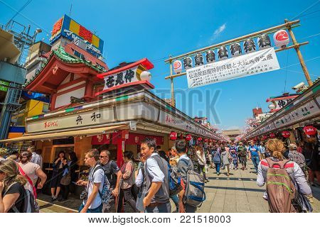 Tokyo, Japan - April 19, 2017: crowd of people in spring sakura on Nakamise-dori, a street with food and souvenirs shops, connetting the Kaminarimon Gate at the entrance of popular Senso-ji Temple.