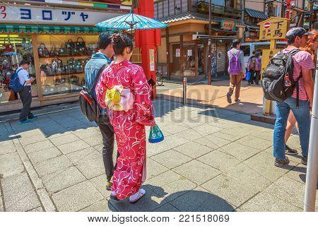 Tokyo, Japan - April 19, 2017: woman wearing kimono with parasol, the national tradition costume of Japan, walking on Nakamise-dori, a market street in Senso-ji Temple in Asakusa, a popular landmark.