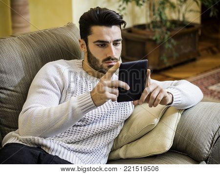 Handsome young man at home smiling, reading with ebook reader lying on a couch