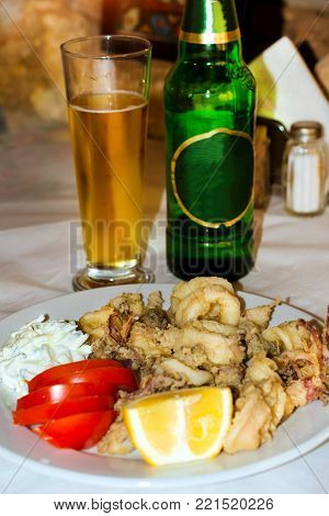 Squid rings and tentacles of octopus fried in batter with salad of fresh tomatoes and slice of lemon. White plate with seafood dish. Mediterranean cuisine and seafood delicacies on island Crete Greece