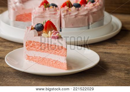 White chocolate strawberry yogurt cake decorated with fresh fruits and chocolate chunk. Sweet pink cake on wood table with copy space. Delicious and sweet pink cake for Valentines or birthday party. Homemade bakery concept. Strawberry cake ready to served